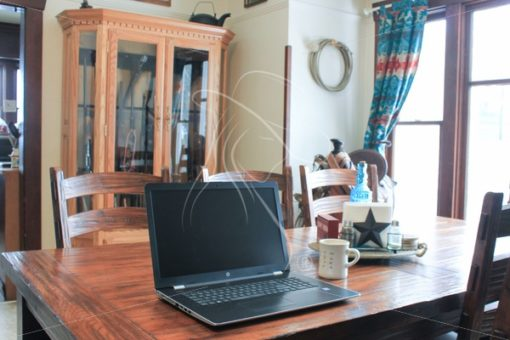 Laptop on dining room table with gun case in background - Theresa Sheridan Designs
