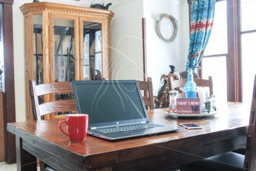 Laptop on dining table in Western setting - Theresa Sheridan Designs