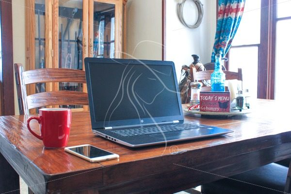 Laptop sitting on dining room table with red coffee mug and iPhone - Theresa Sheridan Designs