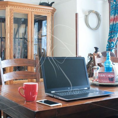 Laptop sitting on dining room table with saddle and gun case in background - Theresa Sheridan Designs