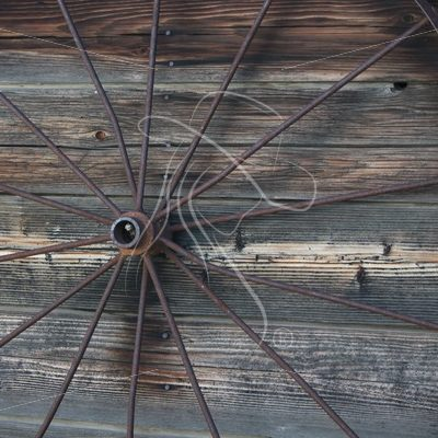Rustic wagon wheel leaning on wood wall - Theresa Sheridan Designs