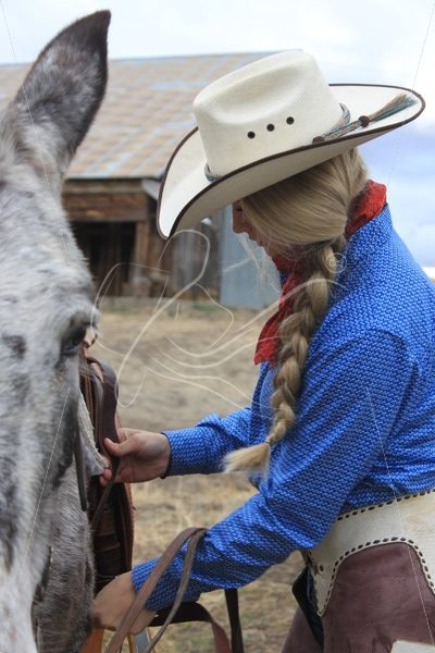 Cowgirl cinching up the saddle - Theresa Sheridan Designs