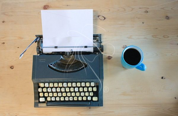 Vintage Typewriter with turquoise coffee mug on wooden table - Cowgirl Media