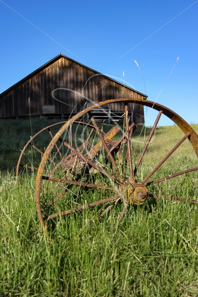 Rusty wagon wheels with barn in background - Cowgirl Media